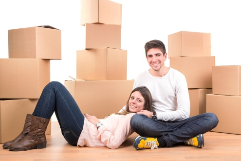 Happy couple with boxes moving into new home apartment